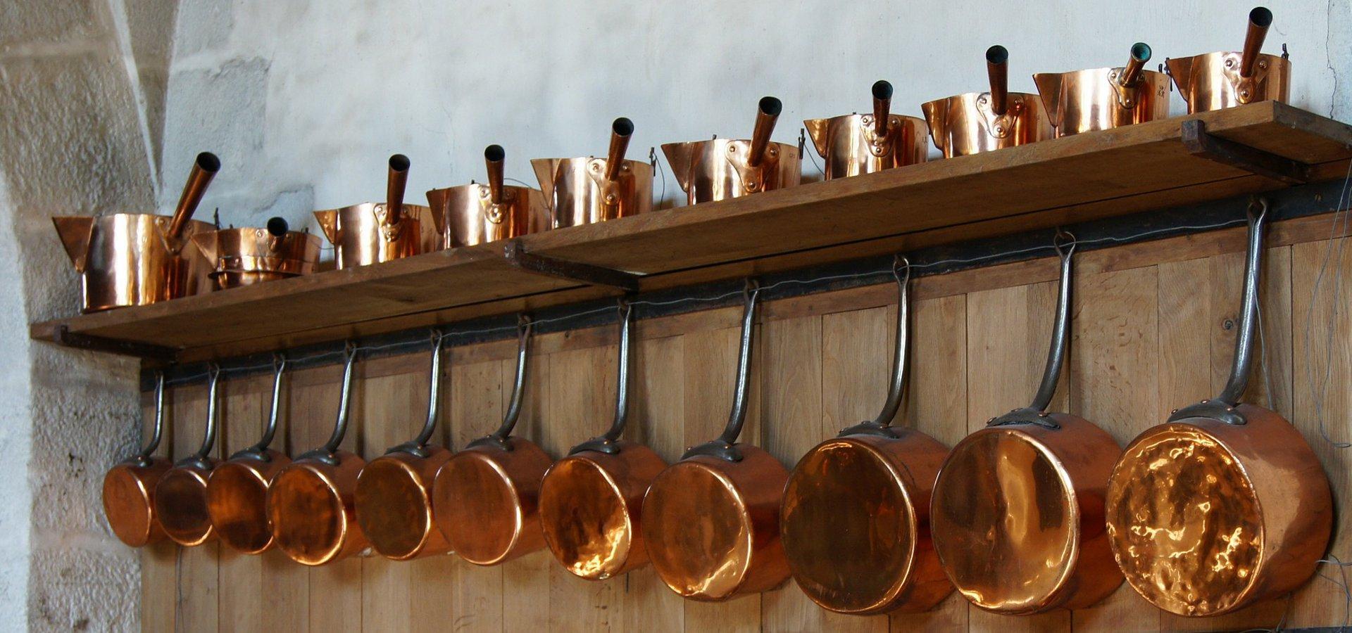 Kupfertöpfe in einer langen Reihe