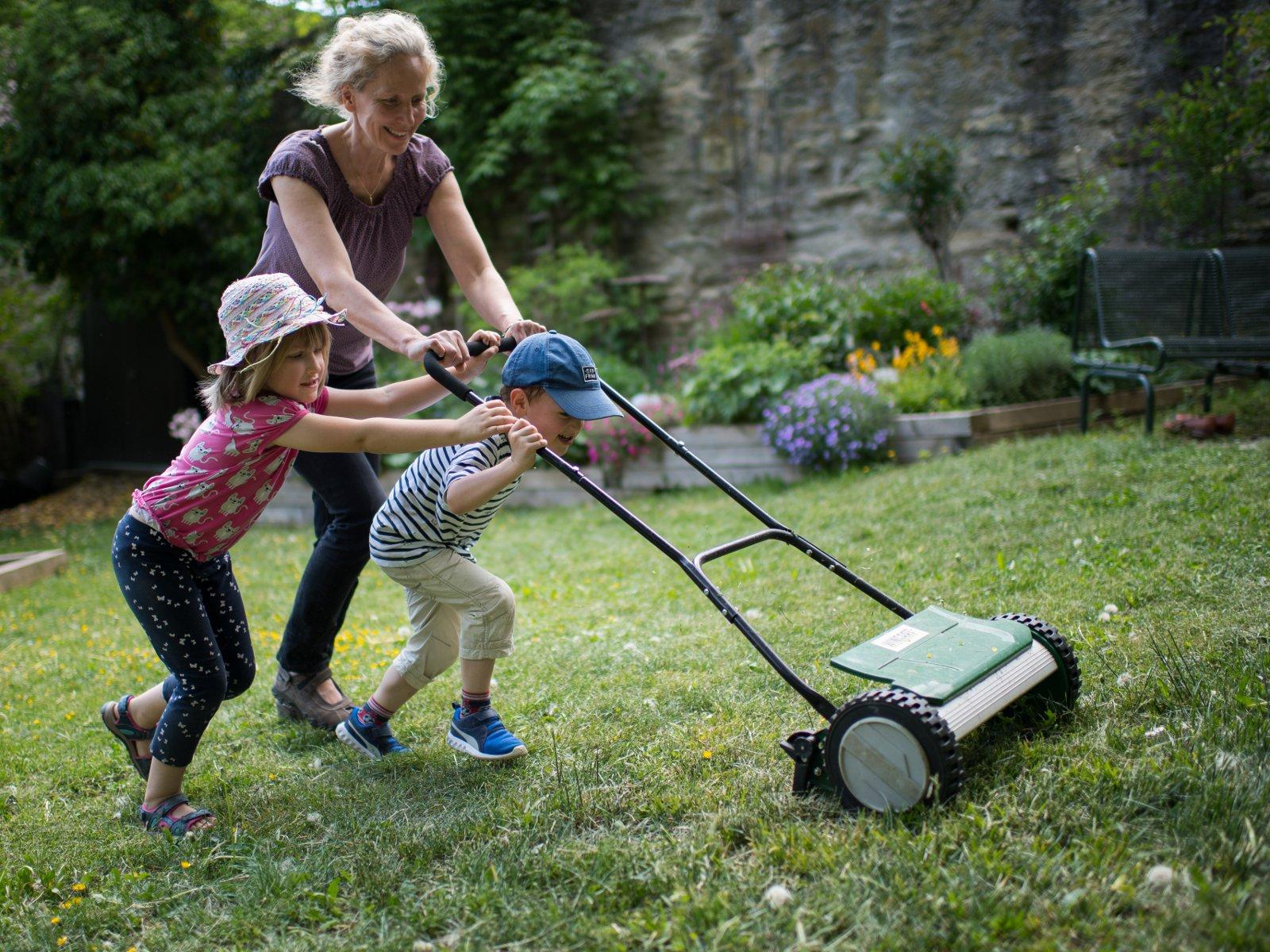 Kinder mähen Gras im interkulturellen Garten