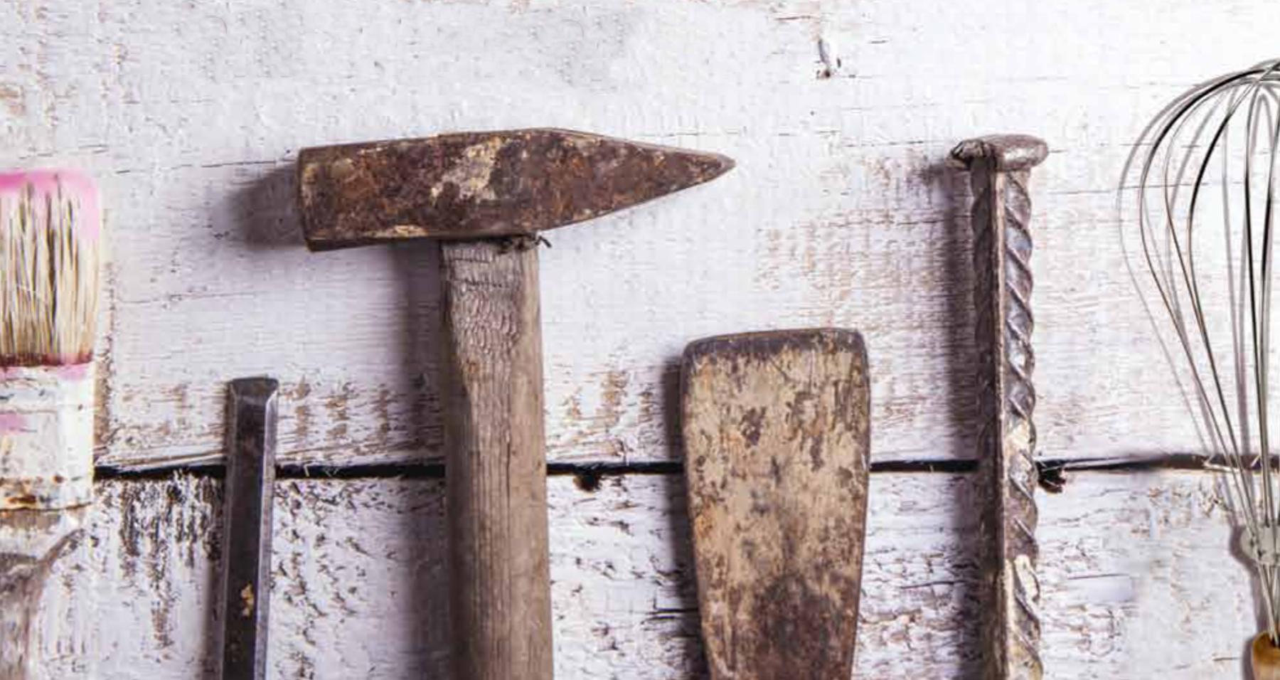 Verschiedene Werkzeuge sind aufgereiht vor einer Holzwand zu sehen u.a. Pinsel, Hammer, Spachtel, Rührbesen