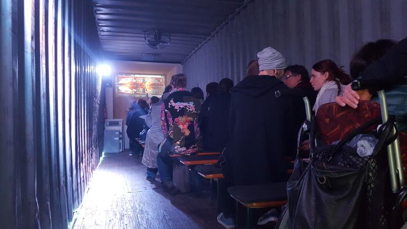 Im Inneren eines Containers sehen Menschen ein Theaterstück über Fluchtursachen