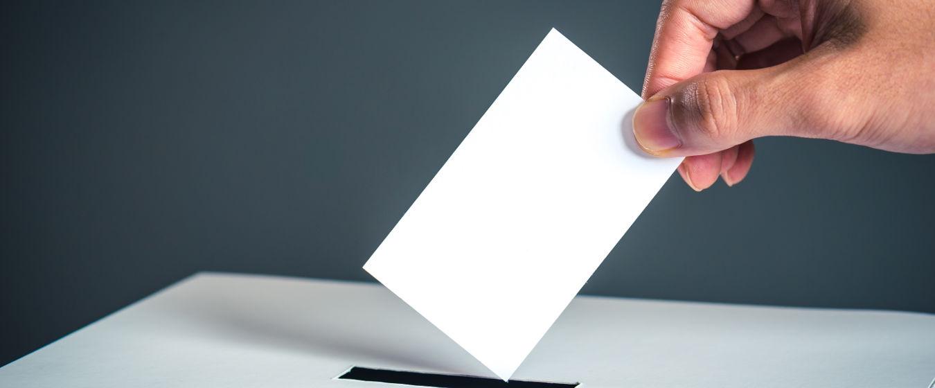 Symbolfoto Wahl: Wahlzettel wird in eine Urne gesteckt