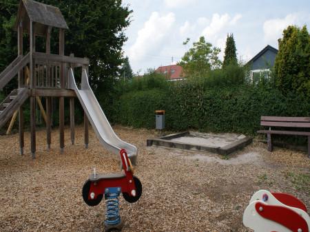 Spielplatz mit Wipptieren, Rutsche und Sandkasten in der Isarstraße