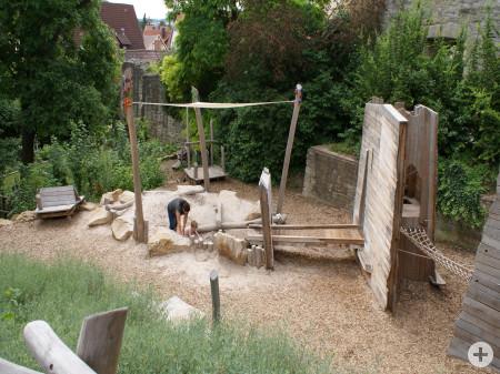 Spiellandschaft mit Sandkasten, Brücke, Rutsche und Klettergerüst