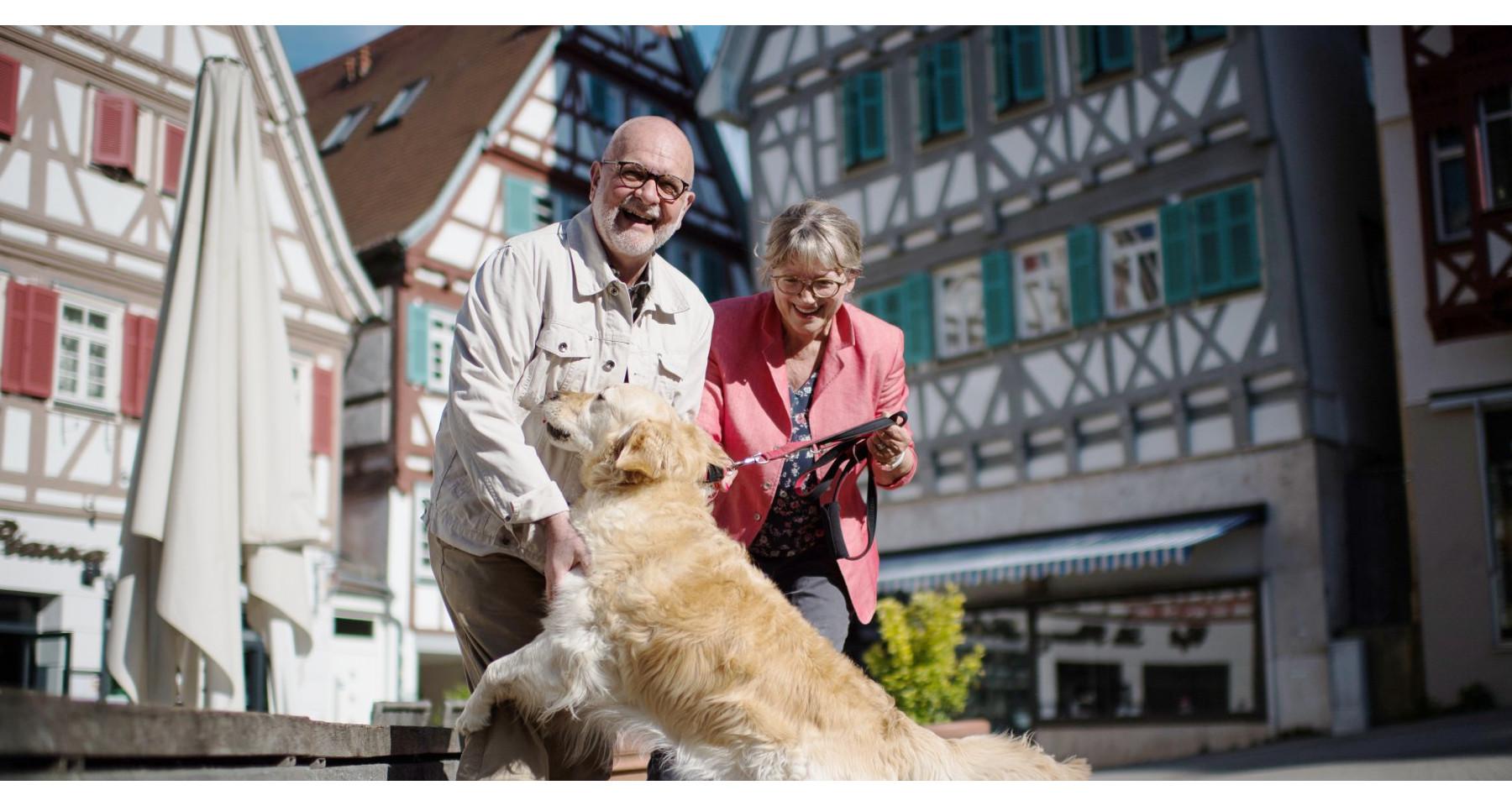 Lachendes Seniorenpaar mit Hund auf dem Marktplatz