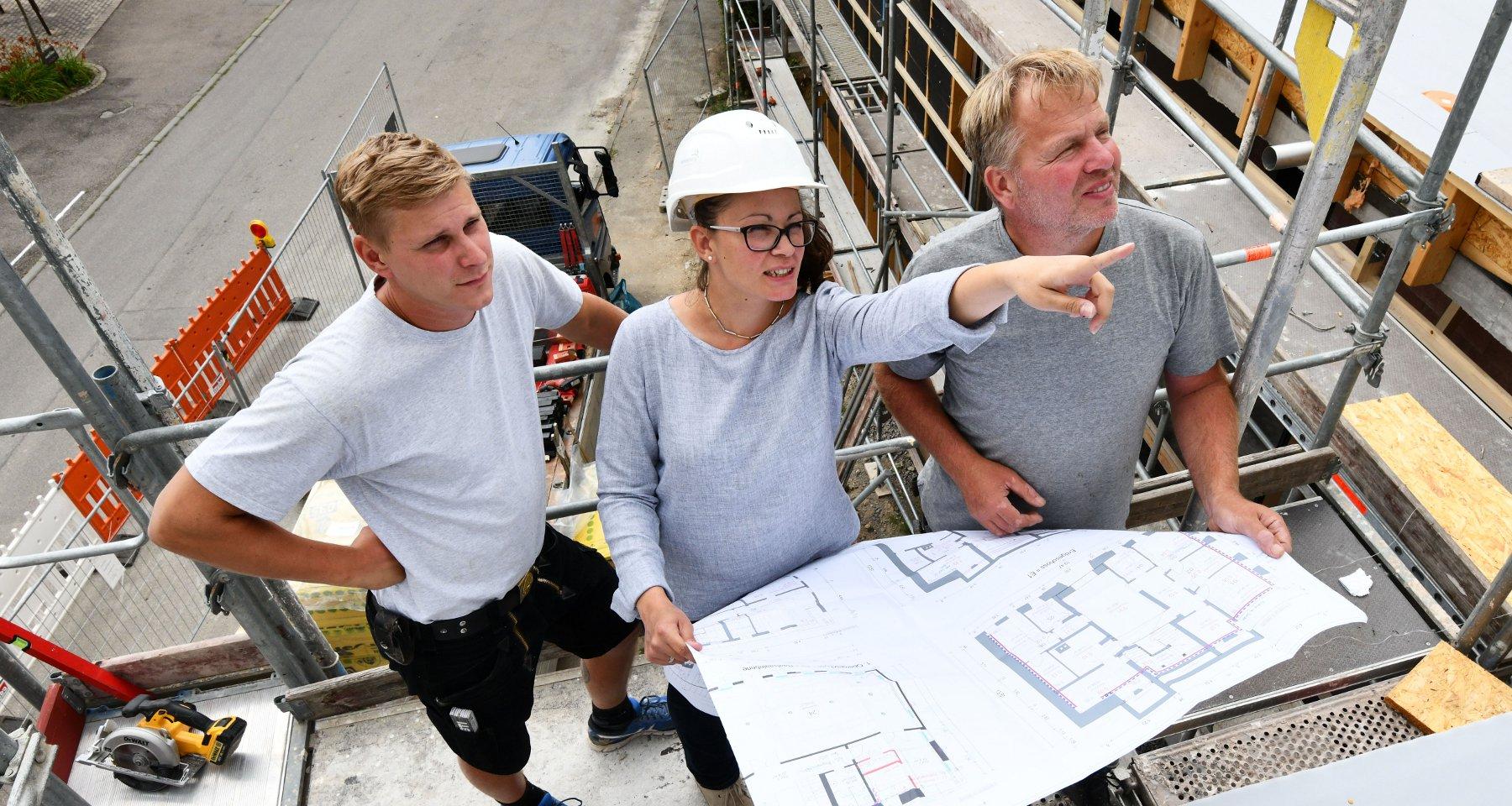 Architektin auf der Baustelle mit zwei Arbeitern