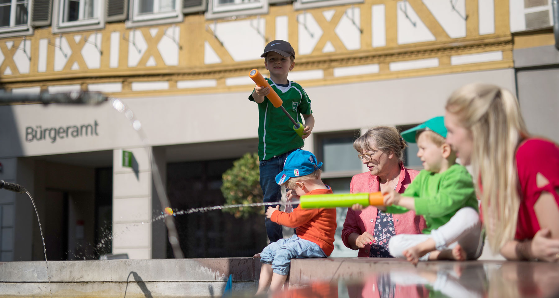 Im Hintergrund das Bürgeramt im Vordergrund Kinder die am Brunnen spielen