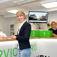 Mitarbeiterinnen im Servicebüro bauen beraten Kunden an der Infotheke