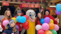 Jugendliche des DLRG mit Maskottchen Freddy Flosse auf dem Herrenberger Weihnachtsmarkt