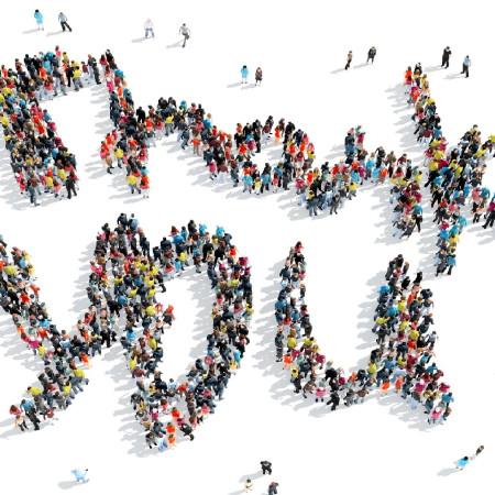 Viele Menschen sind ganz klein nur zu sehen und bilden zusammen die Worte Thank you, auf deutsch Dankeschön