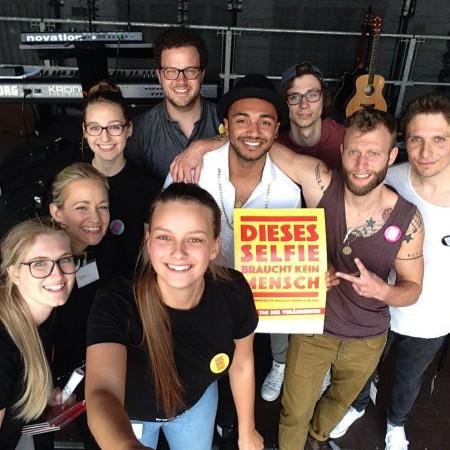 Die Band IZE und das Team Beteiligung machen ein Selfie mit einem Plakat auf dem steht: Dieses Selfie braucht kein Mensch, aber Demokratie braucht dich!