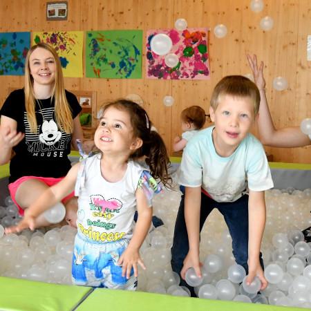 Kinder und Erzieherinnen spielen mit Bällen