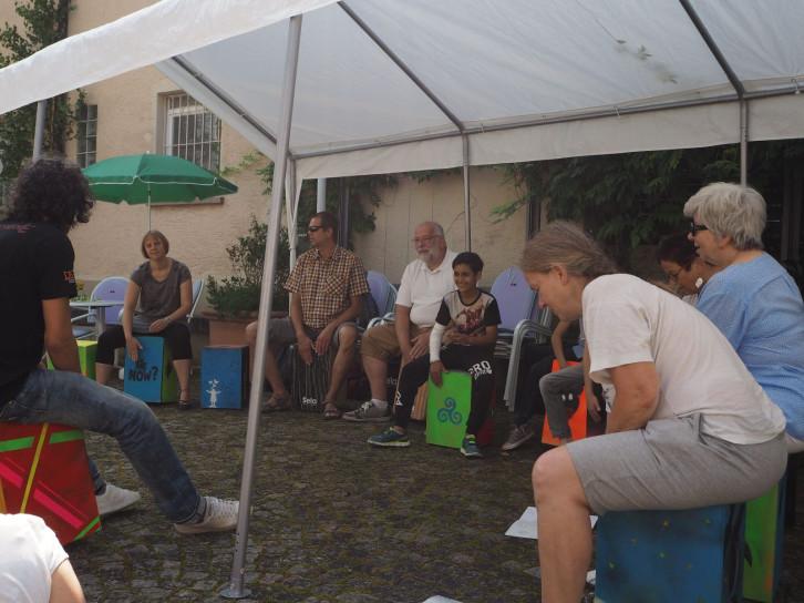 Mehrere Personen sitzen unter einem Zelt auf Cajon Trommeln.