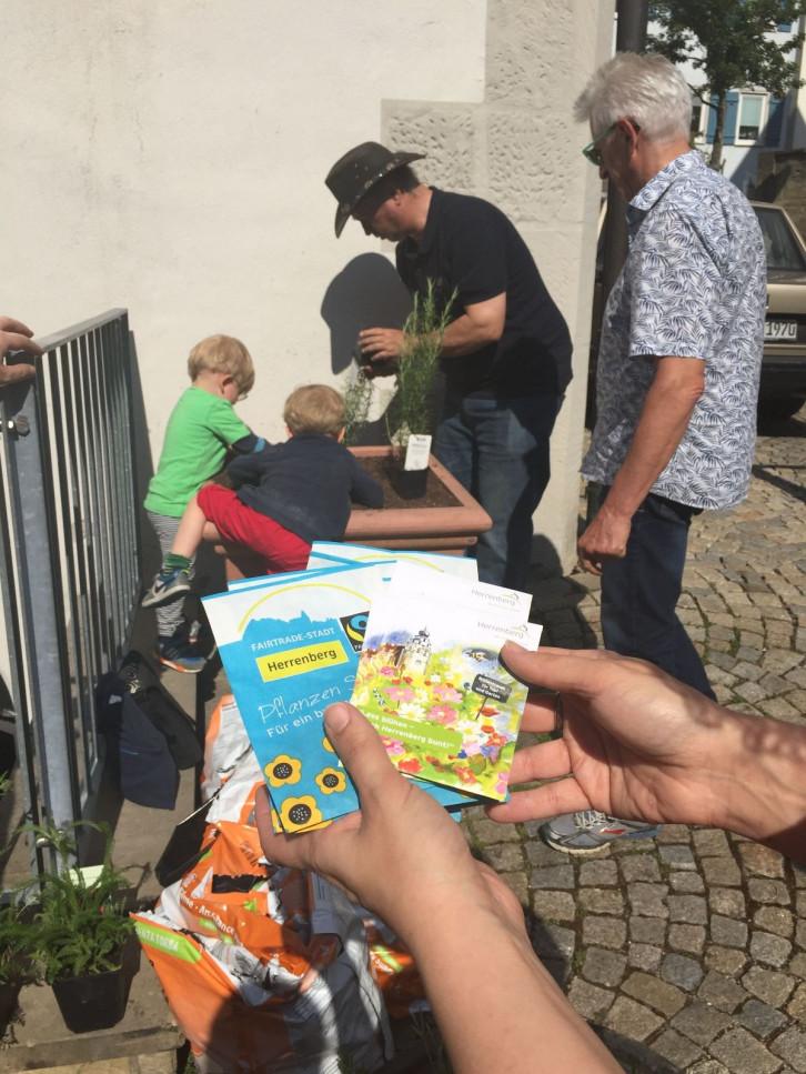 Zwei Kinder und zwei Erwachsene stehen um einen Pflanzenkübel herum. Im Vordergrund hält eine Person mehrere Flyer in der Hand