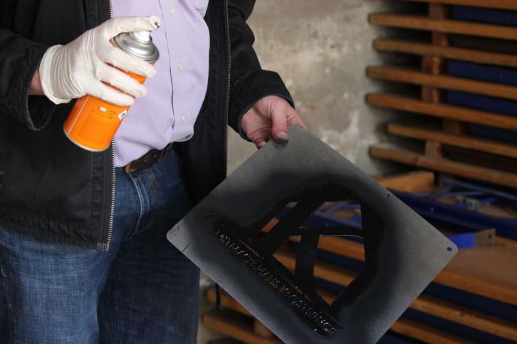 Eine Person hält in der rechten Hand eine organgefarbene Sprühdose und in der linken ein augestanztes Stück Metall.