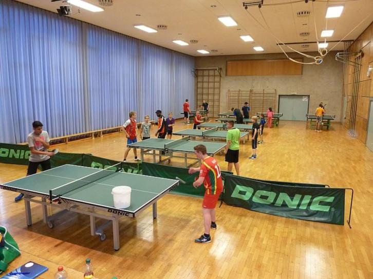 Sporthalle mit Tischtennisplatten und Spielenden