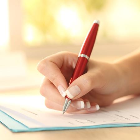 Hand mit rotem Kugelschreiber beim ausfüllen eines Formulars