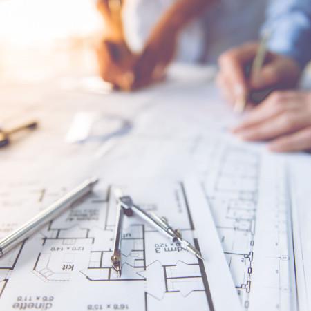 Zwei Hände mit Zirkel und Zeichenstift auf einem Bauplan