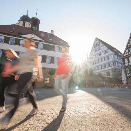 Marktplatz in der Morgensonne mit laufenden Menschen