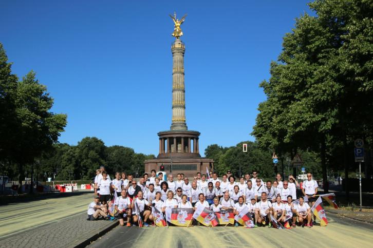Läuferinnen und Läufer des Staffellaufs vor der Berliner Siegessäule