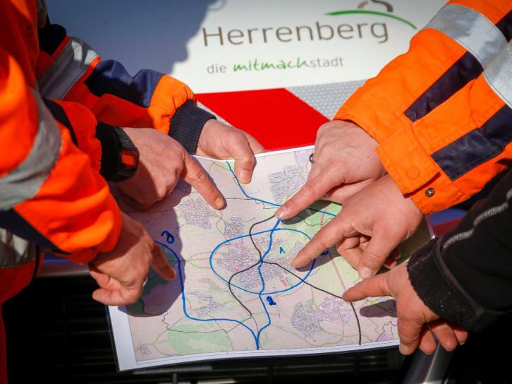 Detailfoto einer Arbeitssituation mit Händen und Plan