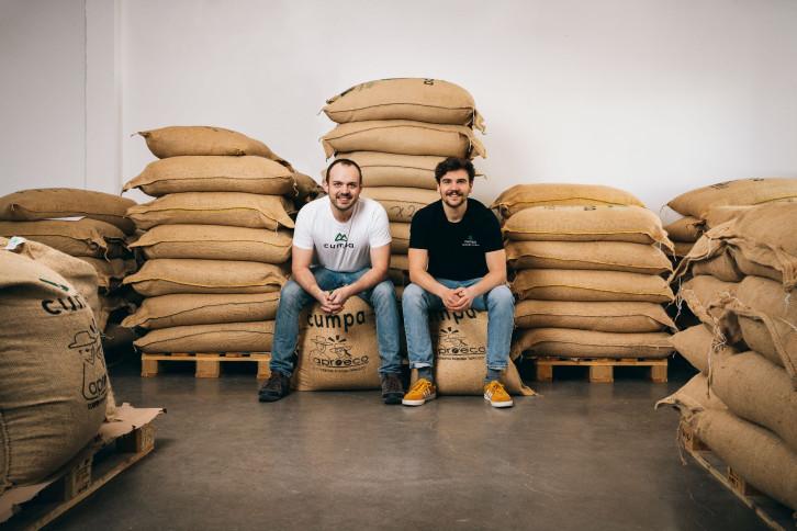 Gründer Lukas Harbig und Daniel Kraus vor Säcken mit importiertem Rohkaffee