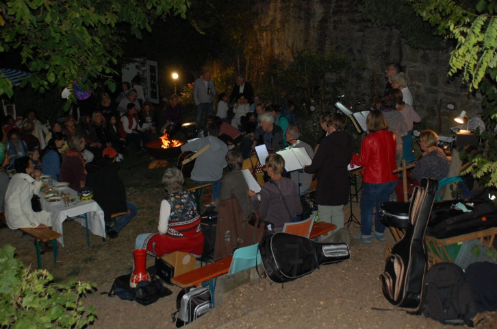 Menschen sitzen um ein Feuer und singen gemeinsam