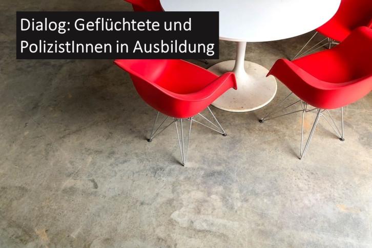 """Rote Stühle am Tisch und die Überschrift """"Dialog: Geflüchtete und PolizistInnen in Ausbildung"""""""