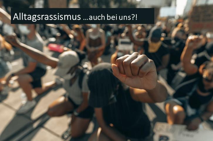 Kniende Menschen strecken die Faust in die Luft, Überschrift: Alltagsrassismus ...auch bei uns?!