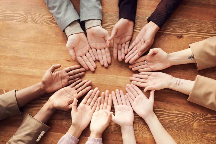 Foto von oben von verschiedenen Händen, die in einem Kreis aus dem Boden liegen