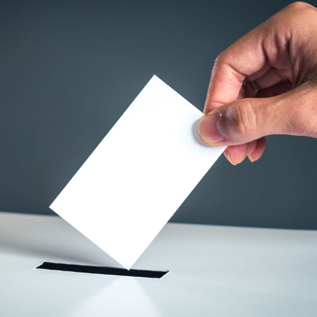 Symbolfoto Hand mit einem weißen Papier über einer Wahlurne