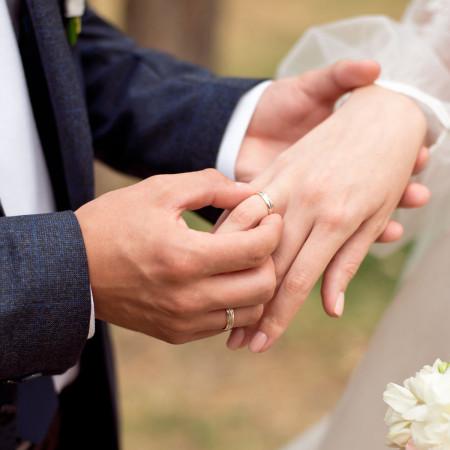 Hand von einem MAnn und einer Frau mit Hochzeitsring